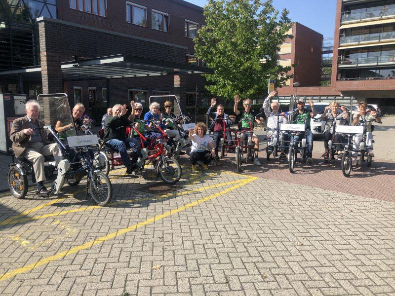 Groepsfoto van alle deelnemers en vrijwilligers op de fietsen.