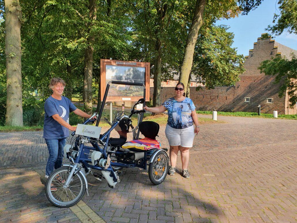Carla en Marijke naast de duofiets en voor het laatste schilderij van de schildersroute.