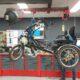 De duofiets hangt aan banden in de werkplaats van fietsenmaker Coen.